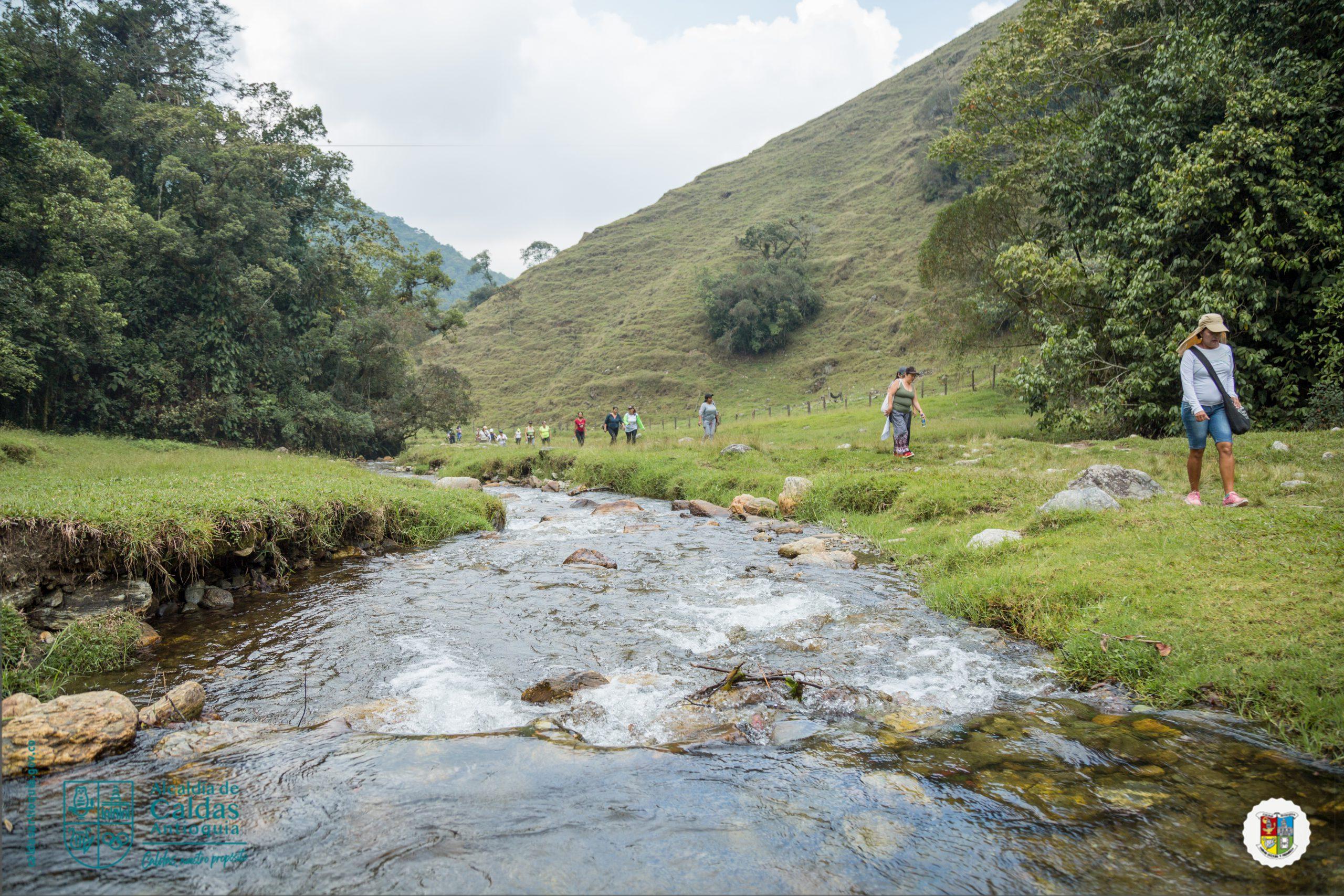 Paisaje, río, montañas y personas recorriendo un camino