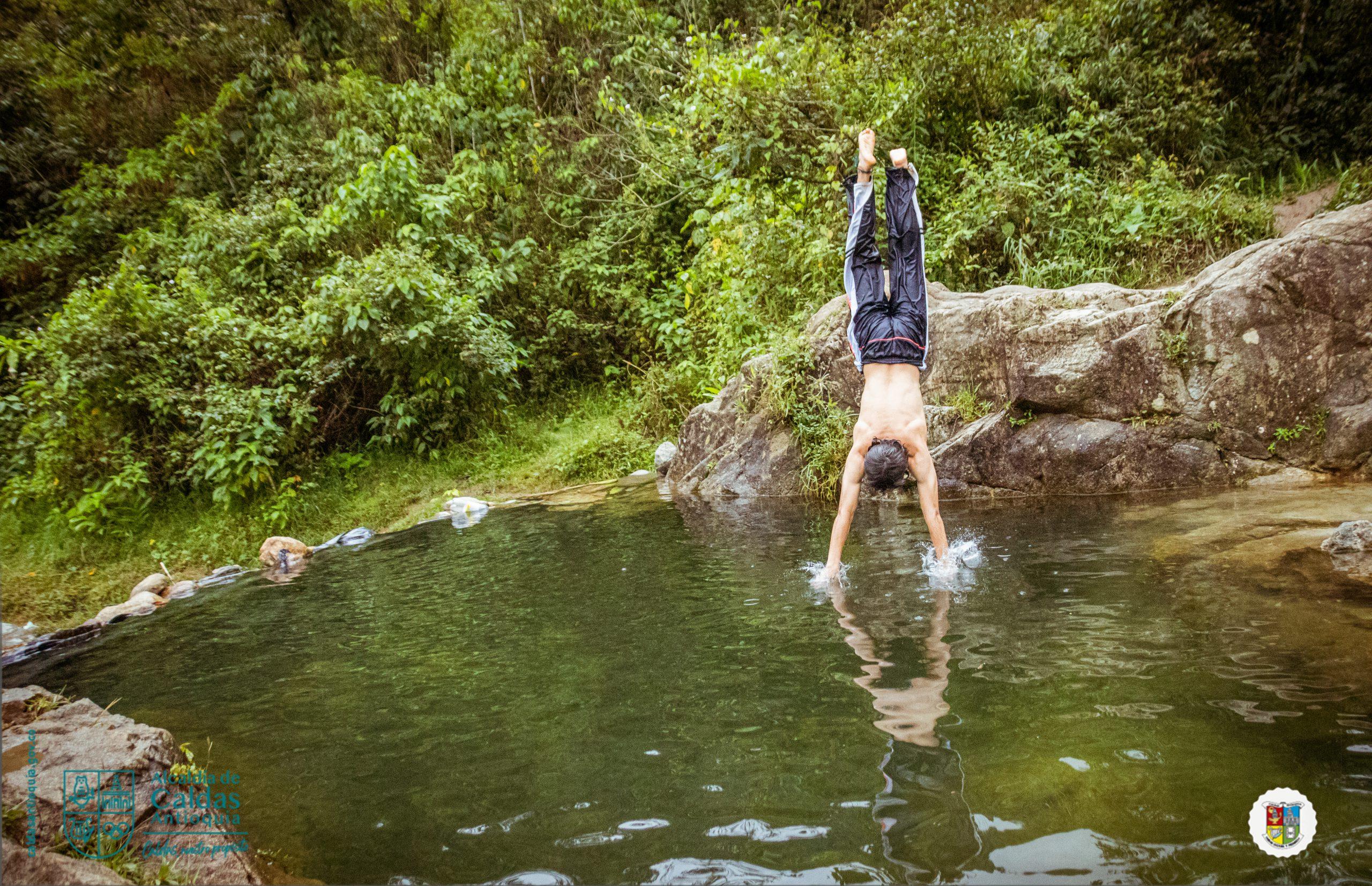 Muchacho parado sobre manos en la orilla de un río